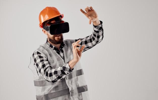 Inżynier budownictwa w okularach wirtualnej rzeczywistości 3d i pomarańczowym kasku na głowie.