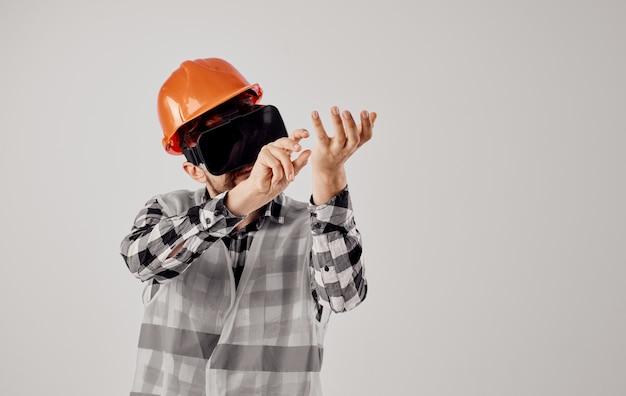 Inżynier budownictwa w pomarańczowej koszuli w kratkę hełm okulary 3d gestykuluje rękami