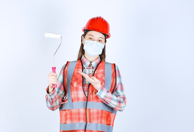 Inżynier budowy kobiet w masce ochronnej i czerwonym kasku trzymającym wałek do malowania