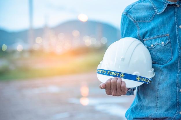 Inżynier budowy w zespole trust suit safety, trzymającym biały żółty kask bezpieczeństwa sprzęt bezpieczeństwa na budowie.