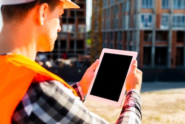 Inżynier budowy widok z boku z bliska za pomocą tabletu