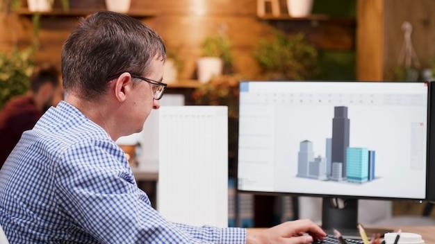 Inżynier człowiek pracujący przy prototypie budynku architektonicznego na komputerze