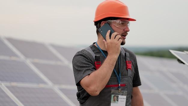 Inżynier człowiek rozmawia przez telefon. młody mężczyzna pracujący zdalnie wśród rzędów paneli słonecznych. pole paneli słonecznych. produkcja czystej energii. zielona energia.