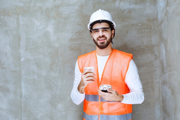Inżynier człowiek w białym kasku i okulary ochronne, trzymając budzik i filiżankę napoju.
