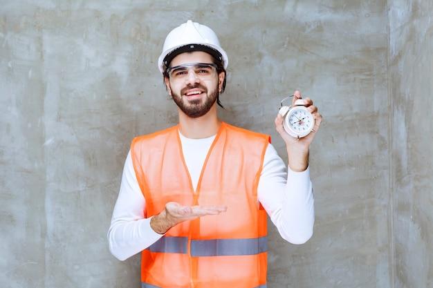 Inżynier człowiek w białym kasku i okulary ochronne trzymając budzik.