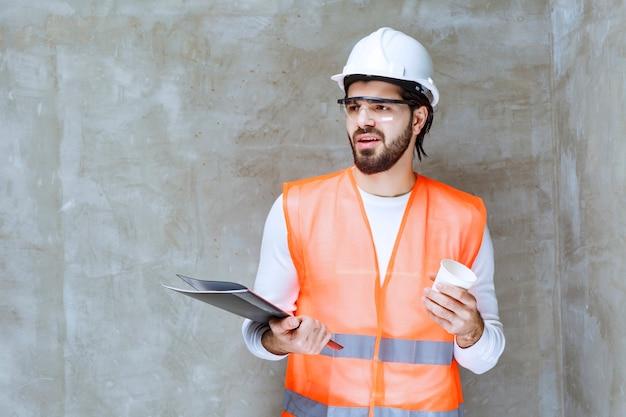 Inżynier człowiek w białym kasku i okulary ochronne, trzymając czarny folder i filiżankę napoju.