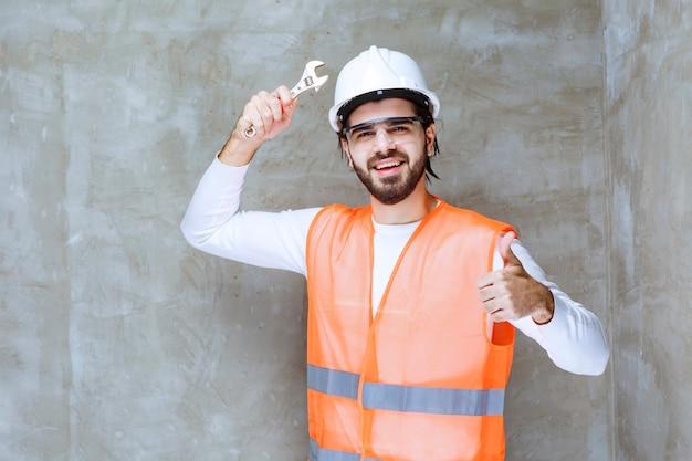 Inżynier człowiek w białym kasku i okulary ochronne trzymając metalowe klucze i pokazując znak przyjemności.