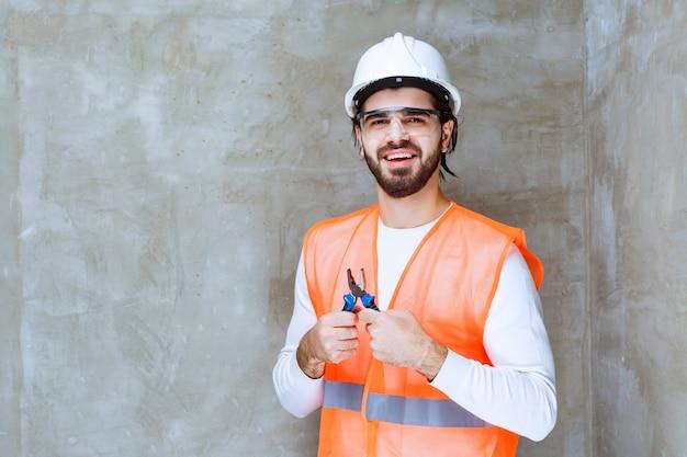 Inżynier człowiek w białym kasku i okulary ochronne, trzymając niebieskie szczypce.