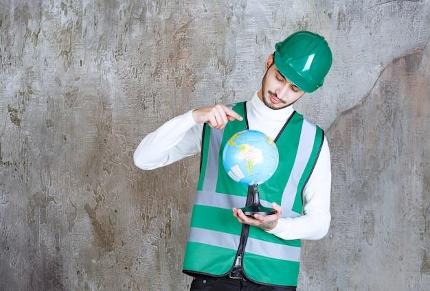 Inżynier człowiek w żółtym mundurze i hełmie, trzymający kulę ziemską i szukający nad nią miejsc.