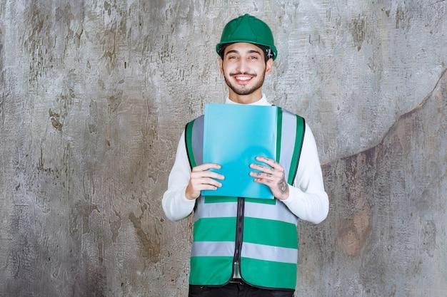 Inżynier człowiek w żółtym mundurze i kasku, trzymający niebieski folder.