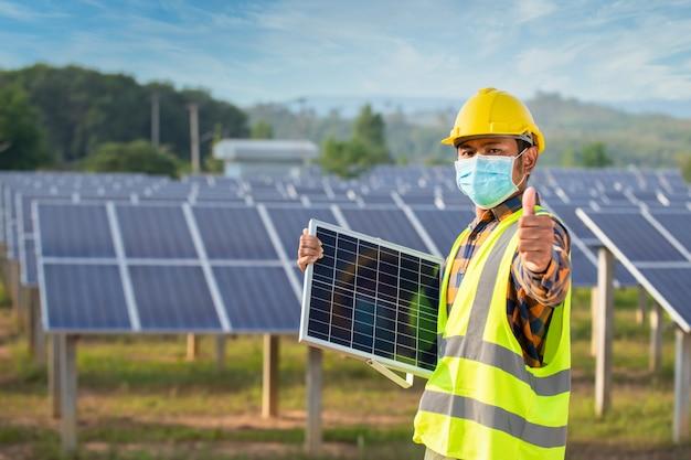 Inżynier ds. energii słonecznej stoi, trzyma ogniwa słoneczne i kciuki w górę, panel ogniw słonecznych z silnym słońcem.