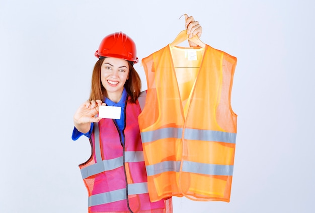 Inżynier dziewczyna w mundurze przedstawiająca koleżance kawałek kurtki ochronnej i prezentując swoją wizytówkę.