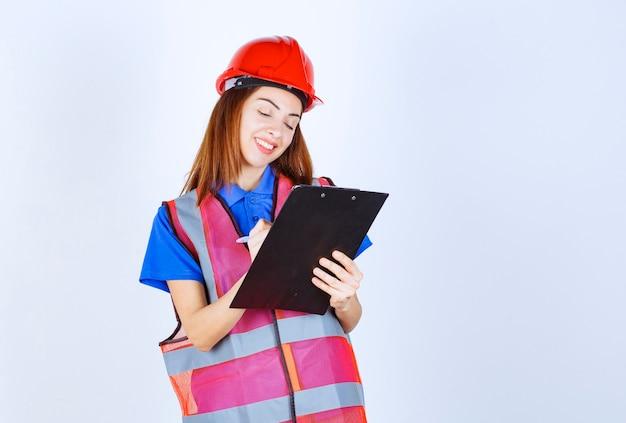 Inżynier dziewczyna w mundurze trzyma listę kontrolną i robi na niej notatki.