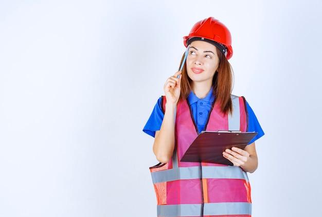 Inżynier dziewczyna w mundurze trzyma plik listy kontrolnej i myśli.