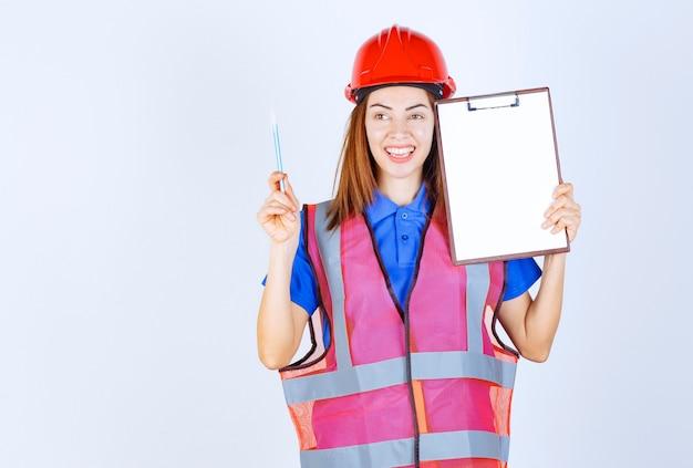 Inżynier dziewczyna w mundurze trzyma pusty plik sprawozdawczy.