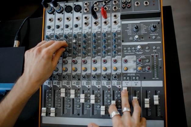 Inżynier dźwięku pracujący przy panelu miksującym w studiu nagraniowym