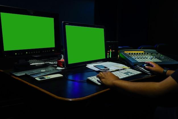 Inżynier dźwięku pracujący w studiu postprodukcji dźwięku i wideozielony ekran