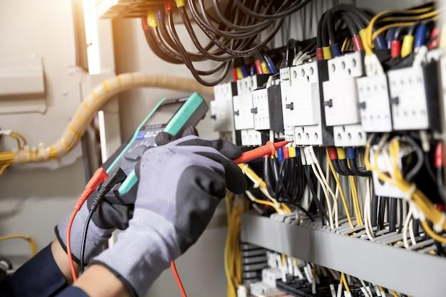 Inżynier elektryk testuje instalacje elektryczne i przewody w systemie zabezpieczeń przekaźników. dostosowanie schematu automatyki i sterowania urządzeniami elektrycznymi.