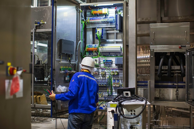 Inżynier elektryk testuje instalacje i przewody maszyny sterującej skrzynką elektryczną w fabryce