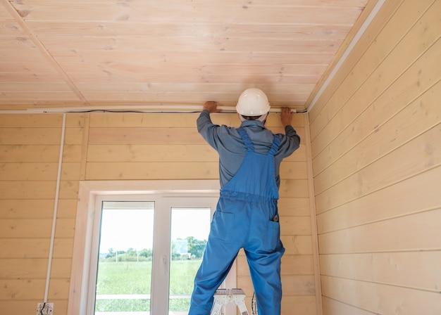Inżynier elektryk wykonuje instalację elektryczną w nowym drewnianym wiejskim domu