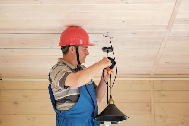 Inżynier elektryk wykonuje montaż lampy sufitowej w nowym drewnianym domu. instalacja oświetlenia elektrycznego w pomieszczeniu