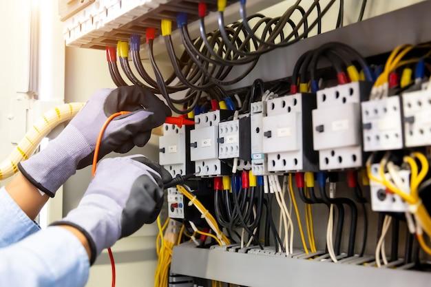 Inżynier elektryk wykorzystujący cyfrowy multimetrowy sprzęt pomiarowy do sprawdzania napięcia prądu elektrycznego na wyłączniku i instalacji kablowej w rozdzielnicy głównej.