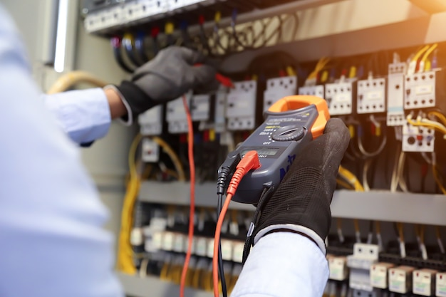 Inżynier elektryk za pomocą multimetru cyfrowego sprawdza napięcie prądu na wyłączniku w głównej tablicy rozdzielczej.