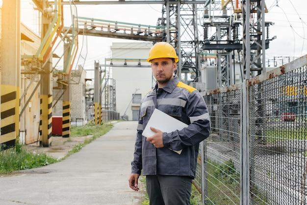 Inżynier energetyki dokonuje przeglądu wyposażenia podstacji. inżynieria energetyczna. przemysł.