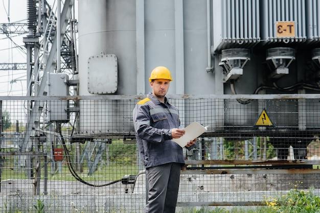 Inżynier energetyki sprawdza wyposażenie podstacji. inżynieria energetyczna. przemysł.