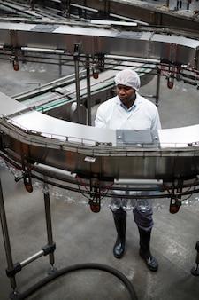 Inżynier fabryki monitoruje linię produkcyjną