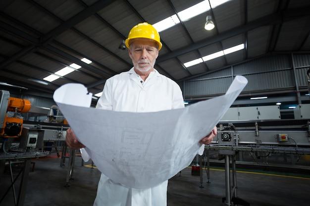 Inżynier fabryki patrząc na plan