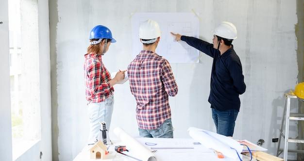 Inżynier i architekci pracujący i dyskutujący na budowie. inspekcja właścicielska przy projekcie wsi i budynku osiedla.