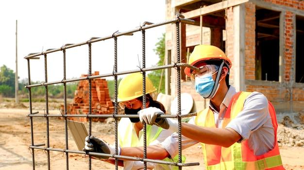 Inżynier i inżynier badają rozmiar i jakość stali używanej na placu budowy