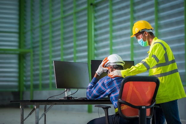 Inżynier i pracownik budowlany noszący maski na twarz w pracy