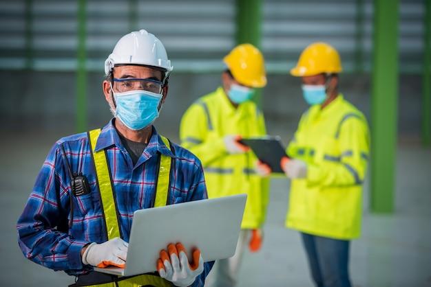 Inżynier i robotnicy budowlani noszący maski na twarz w pracy