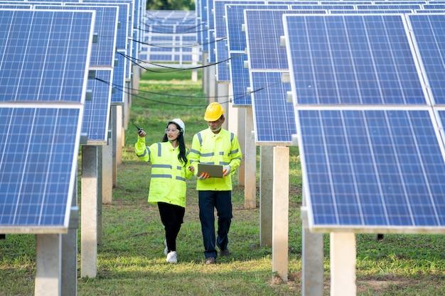 Inżynier i technik sprawdzający sprzęt w panelach słonecznych.