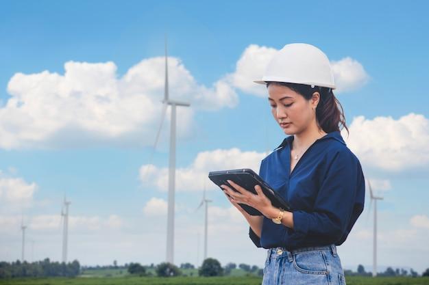 Inżynier kobiet za pomocą tabletu do pracy na miejscu na farmie turbin wiatrowych