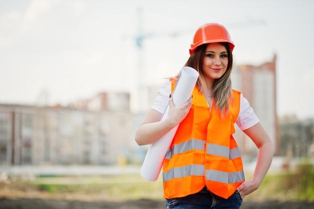 Inżynier kobieta konstruktora w jednolitej kamizelce i pomarańczowym kasku ochronnym trzymać papier firmowy przeciwko nowym budynkom z dźwigiem.