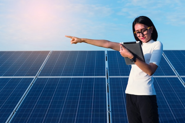 Inżynier kobieta pracuje nad sprawdzaniem stanu sprzętu w elektrowni słonecznej z kartą