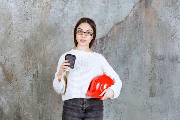 Inżynier kobieta trzyma czerwony hełm i czarny jednorazowy kubek napoju.