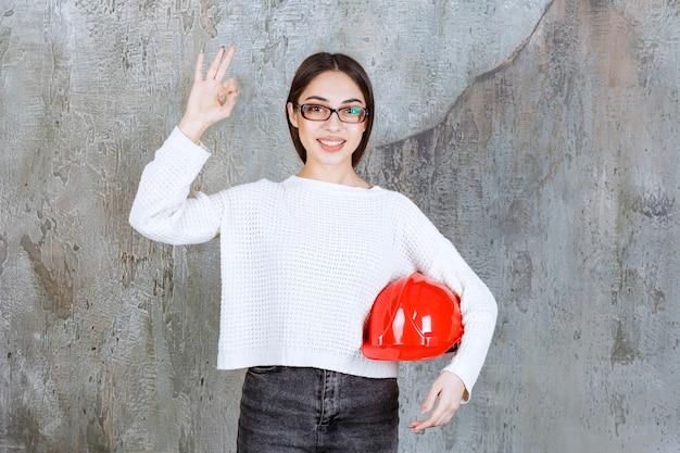 Inżynier kobieta trzyma czerwony hełm i pokazuje pozytywny znak ręki.