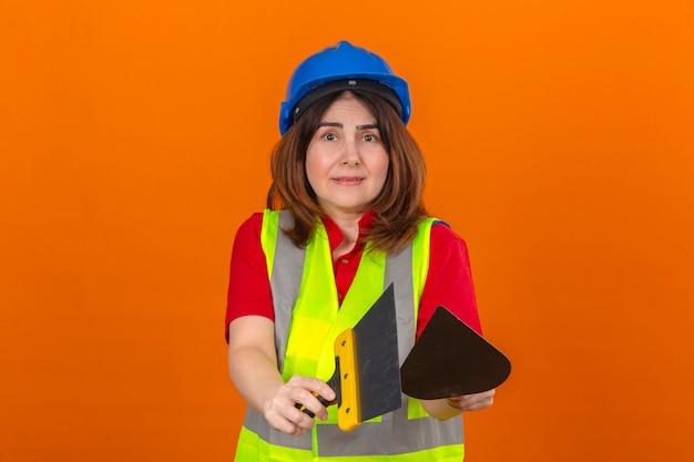 Inżynier kobieta ubrana w kamizelkę budowlaną i hełm ochronny wyciągająca kielnię i szpachlę w dłoniach wyglądająca na zdezorientowaną na odizolowanej pomarańczowej ścianie