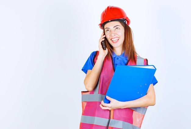 Inżynier kobieta w czerwonym kasku rozmawia przez telefon.