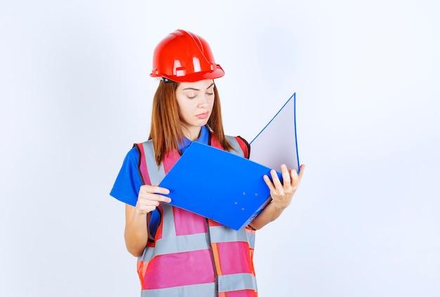 Inżynier kobieta w czerwonym kasku trzyma niebieski folder projektu.