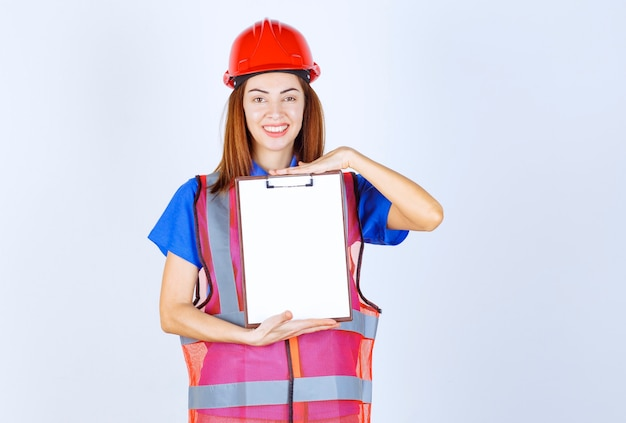 Inżynier kobieta w mundurze trzyma pusty plik sprawozdawczy.