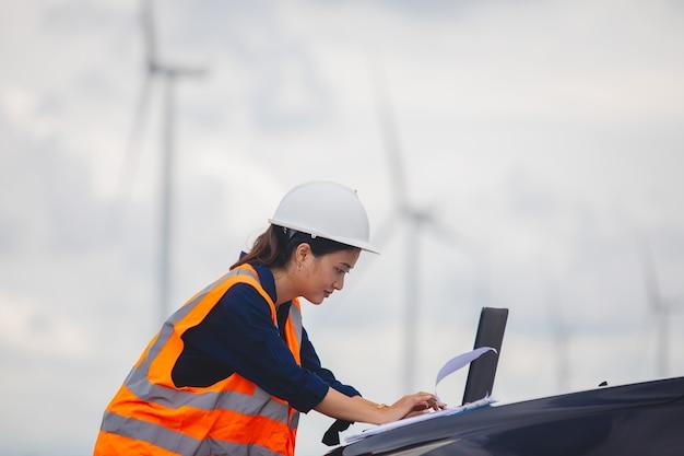 Inżynier kobiety używający telefonu komórkowego i laptopa do pracy na miejscu w farmie turbin wiatrowych