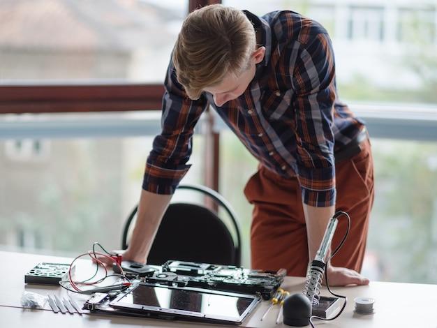 Inżynier komputerowy stojący nad zdemontowanym laptopem. rozwój projektowania elektroniki naukowej