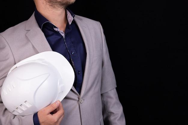 Inżynier, konstruktor, biznesmen w białym hełmie na ciemnym tle. portret. pojęcie inżynierii, biznesu, budownictwa, życia miejskiego i przyszłości.