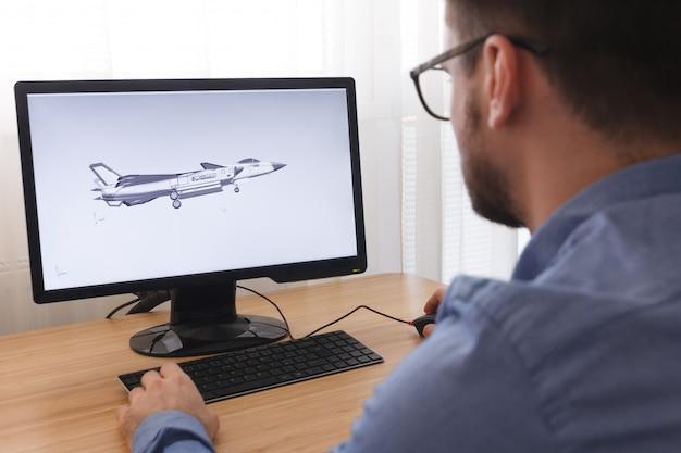 Inżynier, konstruktor, projektant w okularach, pracujący na komputerze osobistym. tworzy, projektuje nowy model 3d samolotu, samolotu w programie cad. praca niezależna