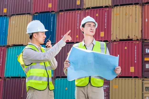 Inżynier kontroluje ładowanie kontenera z importu statku towarowego